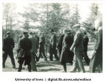 Officials walking among pine trees, Siberia, 1944