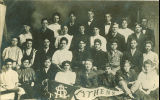 Men and women posing with an Athens pennant at Lenox College, Hopkinton, Iowa, 1900s