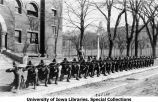 ROTC rifle squad posing with rifles at south entrance of Old Armory, The University of Iowa, 1917