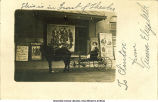 Woman seated in carriage outside theater, West Liberty, Iowa, November, 1915?