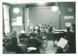 First graders with teacher on stage, The University of Iowa elementary school, March 1958