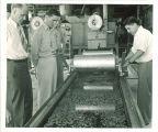 Examining water flow in Hydraulics laboratory, The University of Iowa, 1940s