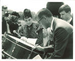 Man signing drum for Scottish Highlanders, The University of Iowa, 1960s