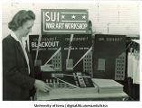 Art instructor Alice Davis examining posters at war art workshop, The University of Iowa, ca. 1942