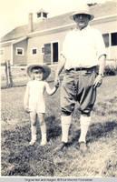 Vidie and George A. Burden behind barn