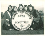 Members of Scottish Highlanders grouped around bass drum, The University of Iowa, 1948