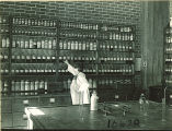 Student reaching for bottle in pharmacy laboratory, The University of Iowa, 1930s