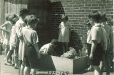 First graders watching a student feed a chicken, The University of Iowa elementary school, May 1932