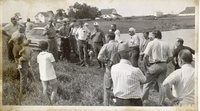 Unidentified Man with Glasses Talks to Group Standing Beside Farm Pond