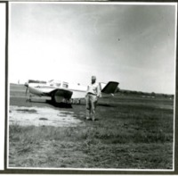 Man Poses in Front of an Airplane