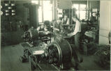 Students working with mechanical devices in basement of Physics Building, The University of Iowa, 1920s