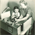 Girl and researcher playing with dollhouse, The University of Iowa, November 11, 1940