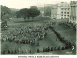 Commencement procession on Pentacrest with crowd looking on, The University of Iowa, 1945