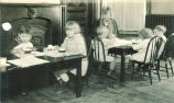 Children sitting at small dinner tables with a woman, The University of Iowa, 1920s