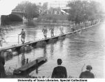 Military personnel walking across bridge over Iowa River constructed by cadets, The University of Iowa, 1929