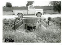 Wilbur Allender standing in front of road culvert structure, 1956