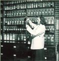 Pharmacy student pouring liquid pharmaceutical, The University of Iowa, 1940s