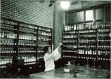 Student preparing drug in pharmacy laboratory, The University of Iowa, 1930s