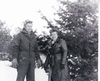 Unidentified man and woman standing near evergreen tree