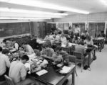 Botany students looking through microscopes and taking notes in classroom in Bessey Hall, 1968