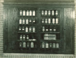 Cabinet of labeled bottles of chemistry compounds, The University of Iowa, 1930s
