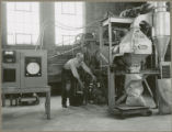 Researcher with the quick curing fertilizer dryer, 1953 or 1954