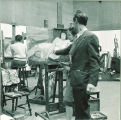 Teacher discussing a painting in progress with an art student, The University of Iowa, 1949