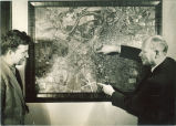 Engineering instructor and student with aerial map of Iowa City in engineering laboratory, The University of Iowa, 1939