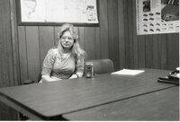 Penny Williams, Volunteer, sits at a table in an office