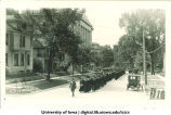 Commencement procession walking north on Capitol Street, with Gilmore Hall on left and Old Dental Building in background, The University of Iowa, June 1922