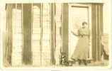 Woman and dog posed in front of hut, Hopkinton, Iowa, April 24, 1913