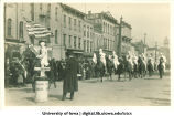 Men in white costumes on horseback in parade, The University of Iowa, 1910s