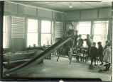 Small children playing on an indoor slide, The University of Iowa, 1920s