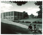 Students on hill across the road from the Law Center addition and original section, the University of Iowa, 1962