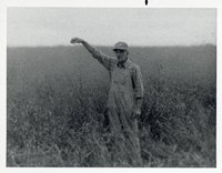 Farmer Wearing Overalls, Hat, and Glasses Stands in  Grassy Field with Arm Extended Above Head