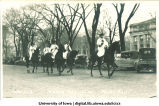 Men with surveying poles on horseback in Mecca Day parade, The University of Iowa, 1920