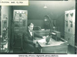 WHAA manager Carl Menzer seated at radio station controls, The University of Iowa, March 13, 1924