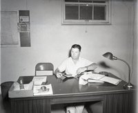 Unidentified Man Sits at Desk in Office