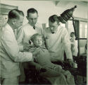 Dental students examining with a small girl, The University of Iowa, 1940s