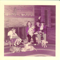 Unknown child, Frindy and John, Sr. sitting with stuffed animals and corgy