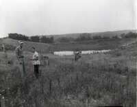 Two unidentified men stand in field by pond