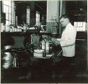 Pharmacy student preparing drugs in laboratory, The University of Iowa, 1940s