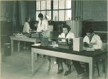 Students working with various equipment in pharmacy laboratory, The University of Iowa, 1930s