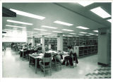 Students studying at tables in the reference section of Main Library, the University of Iowa, 1970