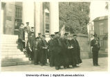 Commencement officials filing out of Old Capitol, with North Hall in background, The University of Iowa, 1910s