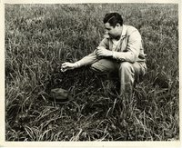 Unidentified man kneeling in grassy field
