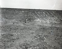 Unidentified Man Looks Down at Pipe in Rocky Soil
