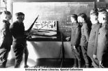 Cadets standing at black board in rifle assembly class, The University of Iowa, 1918