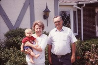 Bob and Joanne Lundquist with their grandson Levi in front of their home.
