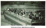 Boat decorated and carrying band members on Iowa River, The University of Iowa, 1920s